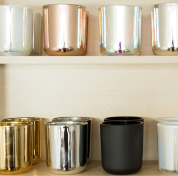 rose gold candle, black candle, silver candle & white candle on shelf