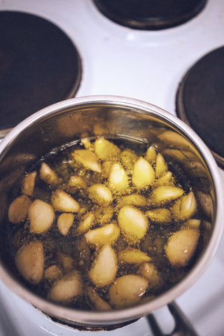 Garlic confit cooking in olive oil
