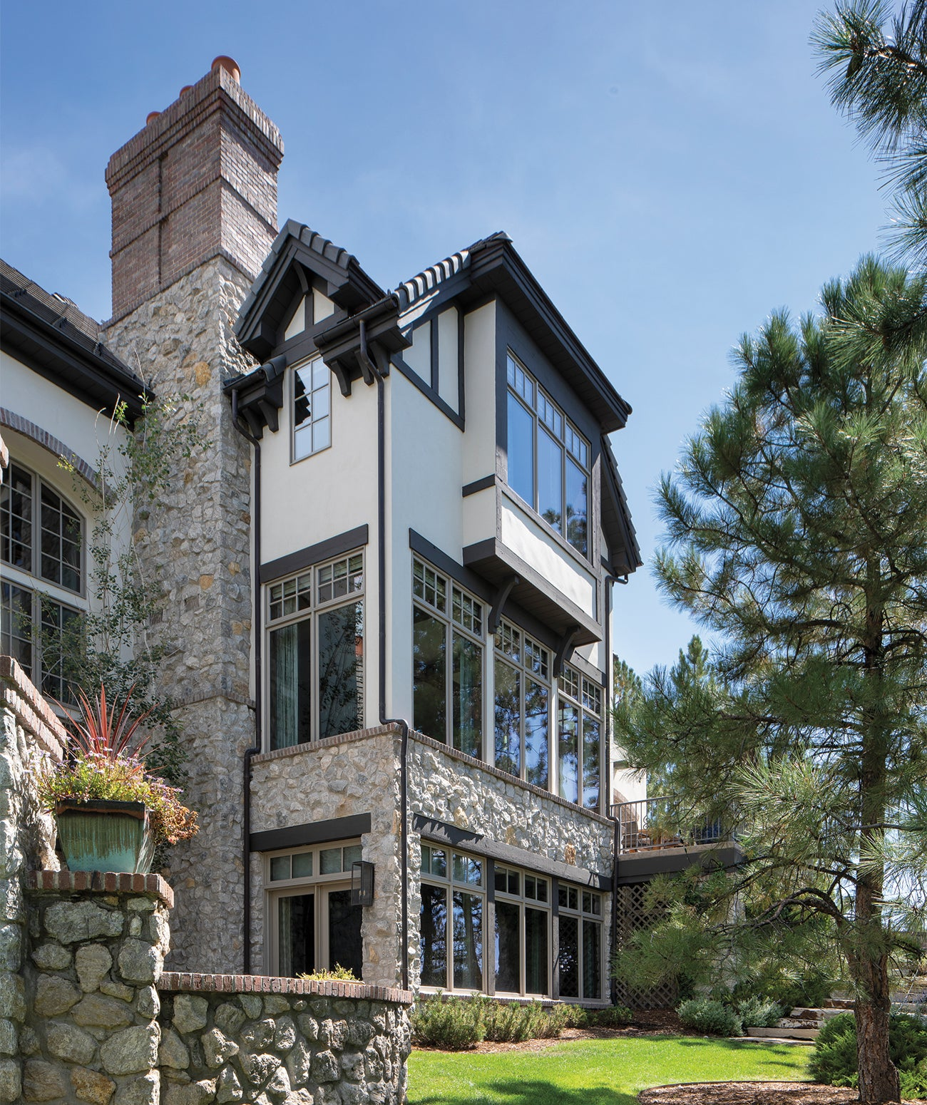 Exterior of a large home with grassy lawn/Photography: Emily Minton Redfield/This Colorado home's stone exterior was updated with design team Marc-Michaels Interior Design painting the stucco Sherwin-Williams' Shoji White and the trim with Sherwin-Williams' Sealskin.