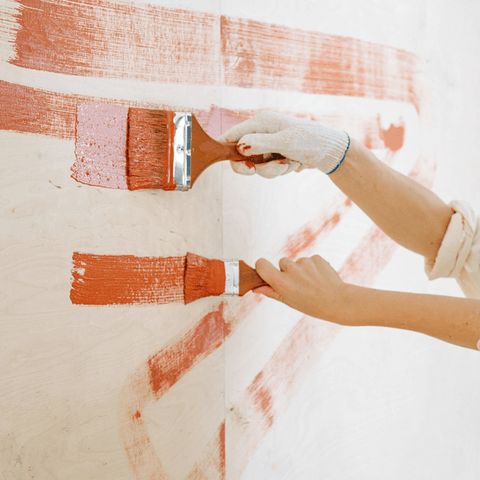 people painting with orange paint