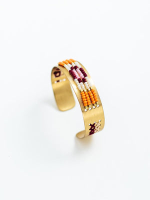 gold toned brass bracelet adorned with purple, pink, white and orange glass beads.  Made by fair trade artisans in India