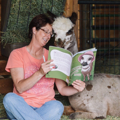 a woman sitting in a barn reading to an alpaca