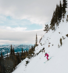 female skier skiing down the mountain in pink onsie