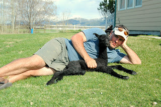 owner james laying in the grass with black baby alpaca