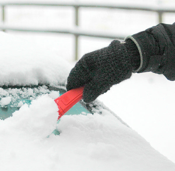 man scraping snow off of car windshield with gray mittens for winter