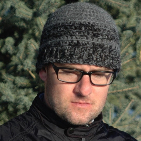 man with glasses wearing gray and black wool hat