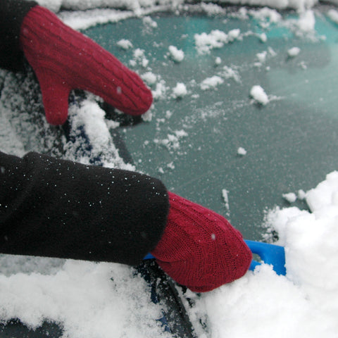 woman brush snow off of windshield with mittens for winter
