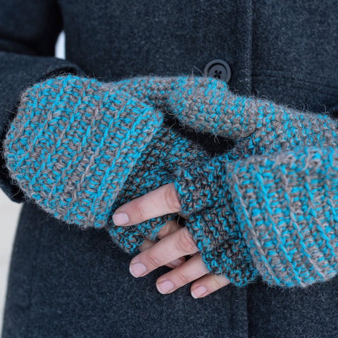 woman in gray coat wearing blue and gray warm winter mittens