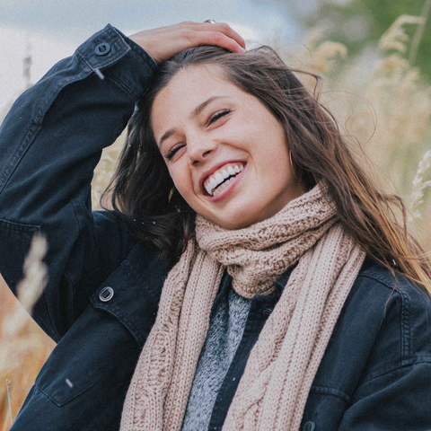 woman smiling while wearing natural brown warm alpaca wool cable scarf