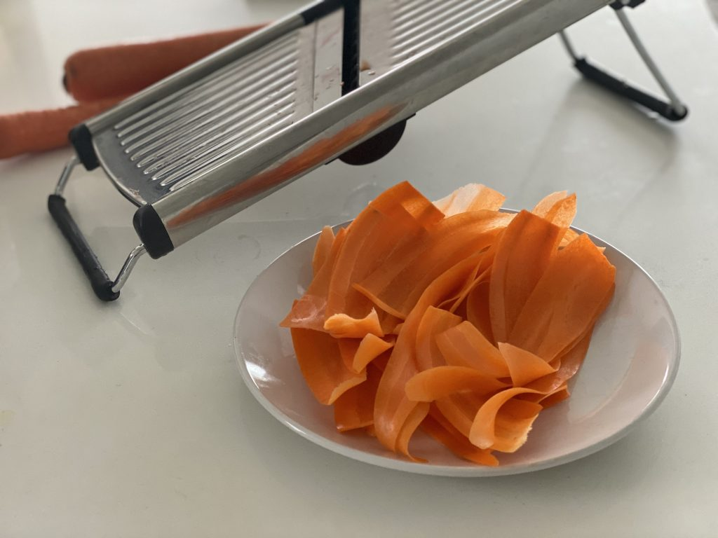 Thinly sliced carrots after being sliced in a mandolin.