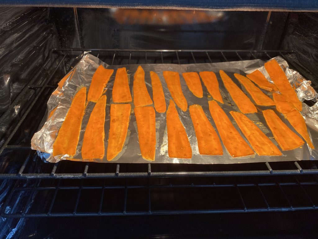 Carrots coated with carrot bacon coating ready to be put into the oven.