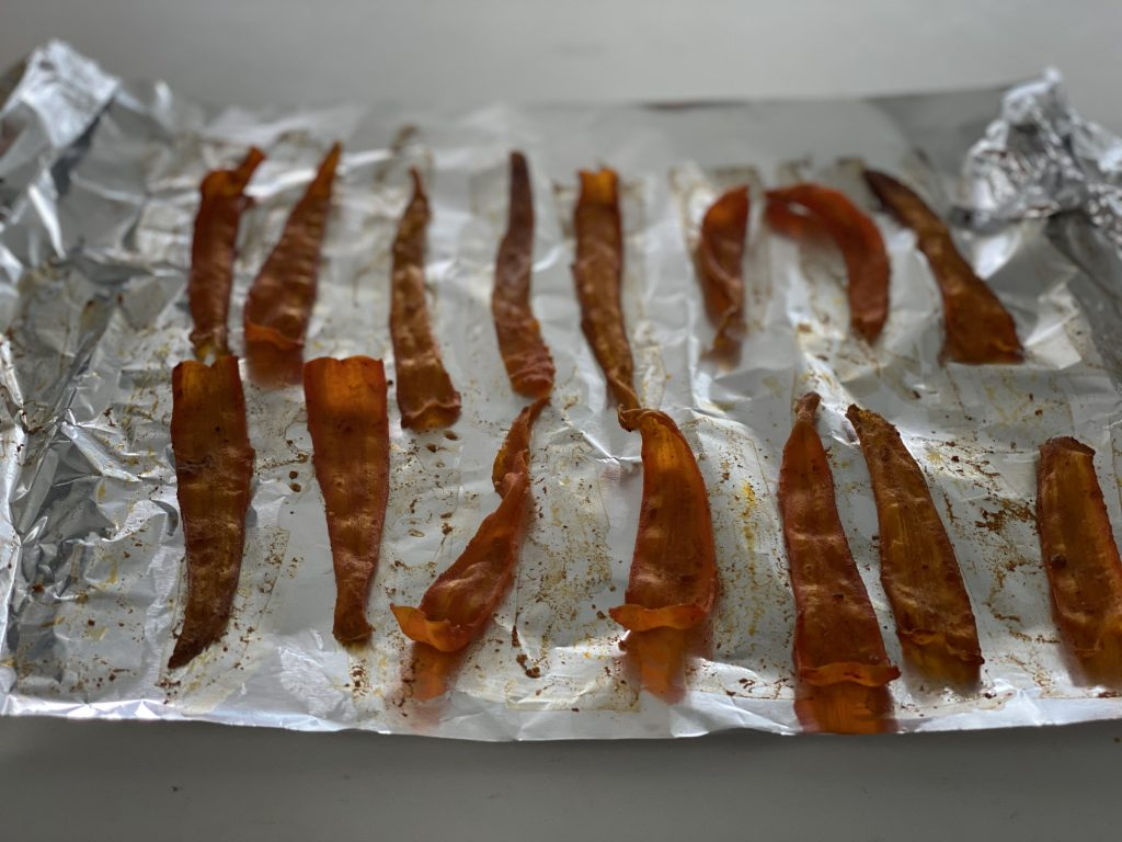 Crispy carrot bacon ready to be snacked on or used as a topping in a healthy plant-based recipe.