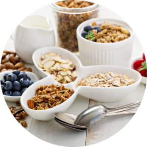 Nutritious plant-based ingredients like almonds, blueberry, and rolled oats are layed out in ramekins on a table.