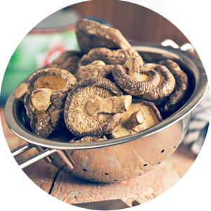 Dried shiitake mushrooms placed in a strainer ready to be added to a flavorful vegetable stock.