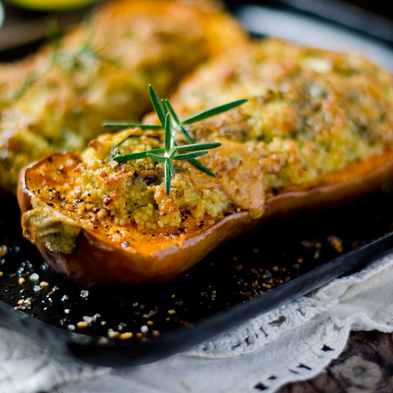 Butternut squash stuffed with plant-based quinoa stuffing for the ultimate plant-based Thanksgiving feast.