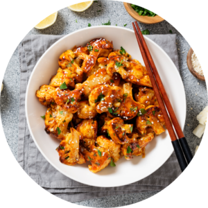 Cauliflower wings are baked and coated with barbeque sauce before plated on a white plate with chopsticks and ingredients around the plate.