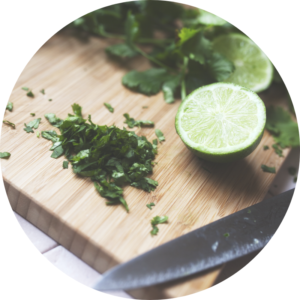 Cilantro and lime are prepared as ingredients for a homemade salad dressing.