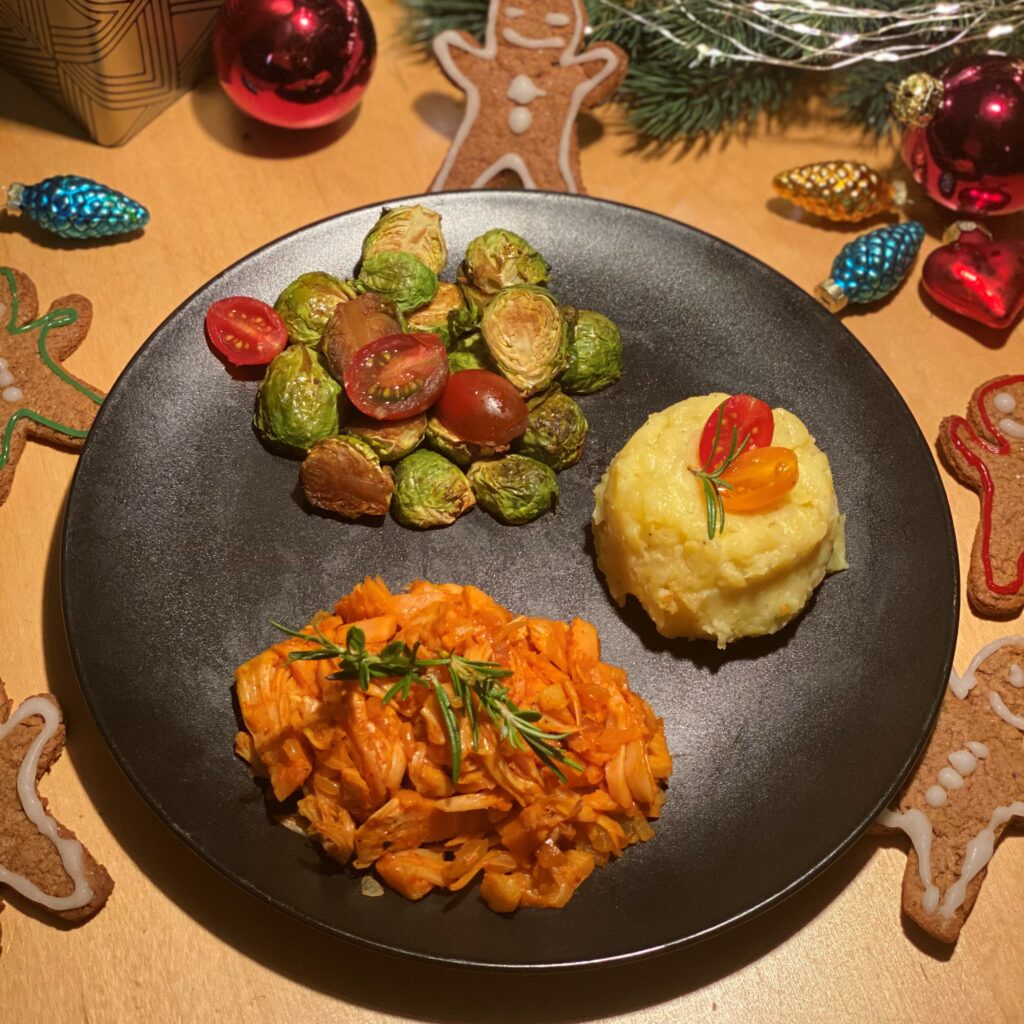 Jackfruit pulled pork is plated with roasted brussel sprouts, cauliflower mash, and surrounded by gingerbread men and Christmas ornaments.