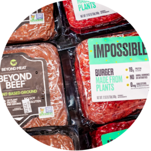 Packages of Beyond Beef and Impossible Burger meat are lined up next to each other.