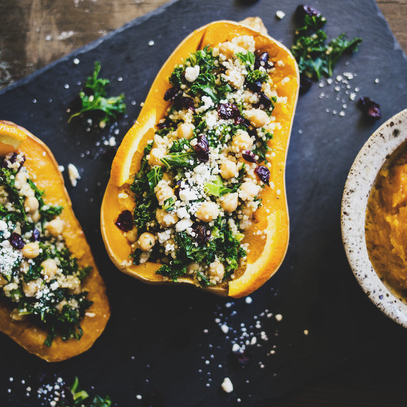 Stuffed butternut squash stuffed with plant-based quinoa stuffing for the ultimate plant-based Thanksgiving feast.