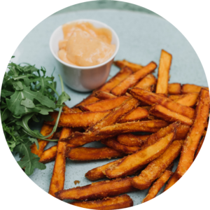 Crispy sweet potato fries laying next to a bed of green salad and spicy almond dip.