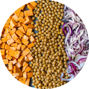Sweet potato, chickpeas, and onion are laid out on a sheet pan ready for roasting.