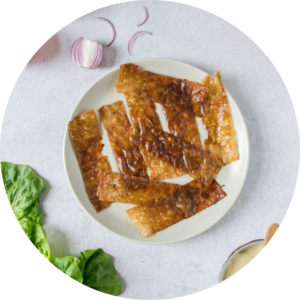 Vegan bacon made using ricepaper is placed on a white dinner plate with loose leaves of lettuce and chopped onion placed around it.
