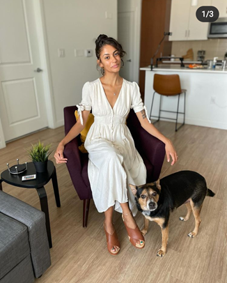 Destiny is wearing a vintage button down white sun dress. She is sitting in a purple chair, and she's accompanied by her dog.