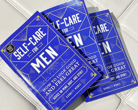 """The picture shows a self-care manual for men. The book is blue and gold, and it says self-care for men: """"how to look good and feel great."""""""