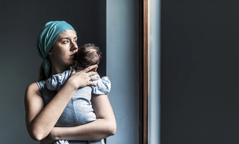 A mother looks out of her window with great worry and apprehension as she looks out of window and holds her baby. A greyness surrounds her.