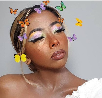 Karishma is wearing light pink lipstick, a white dress, and her hair is in a bun. She wears eyeshadow like the colors of sherbet and matches the butterflies. Animated pink, yellow, and lilac butterflies surround her face as she looks into the distance.
