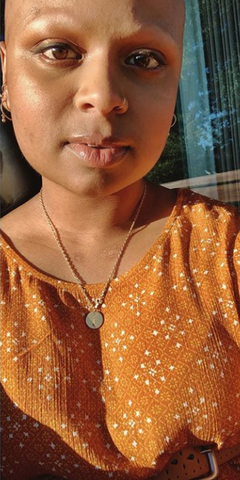 Mohana wears an orange blouse. There is love in her eyes, and she has an expression on her face as if she is amazed.