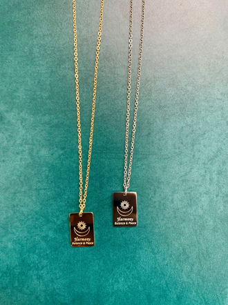 This picture shows two gold necklaces. They show a sun and a moon, and it says harmony.