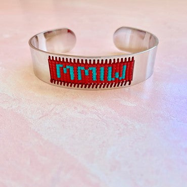 """This bracelet is a gold slip-on clasp. That has a blue and gold knit fabric that says """"MMIW."""""""