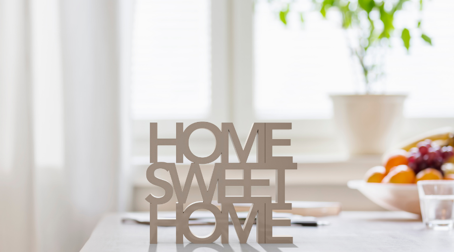 White curtains with a plant on a table and wooden wording on stating Home Sweet Home