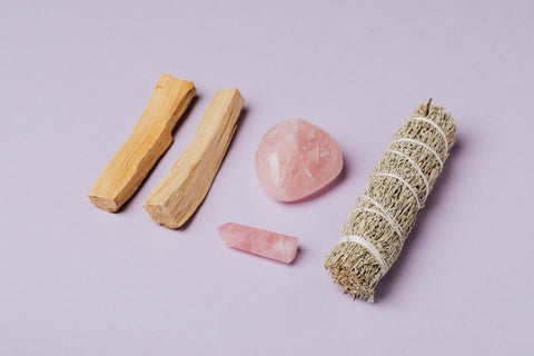 Tools for cleansing your energy. Palo Santo wood, rose quartz and a sage bundle on a pink background.