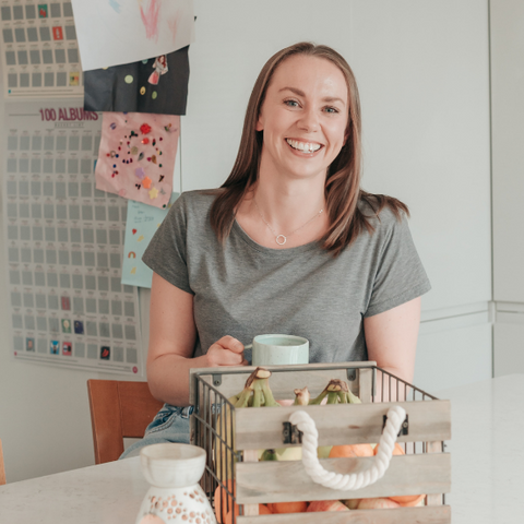 KIT founder, Annabel, sat in her kitchen holding a cup of tea and smiling at the camera.