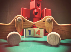 Bajo dachshunds with noses rubbing together.  Red heart cut-out blocks and number blocks in background.