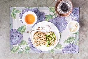 Ekelund Weavers of Sweden Blå Hortensia placemat, with plate with bun with avacado, teacup and teapot with honey.