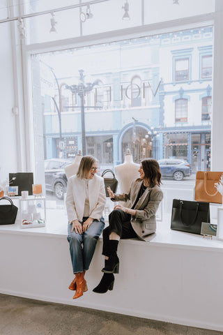 Co-founders laughing in the window of Violette Boutique on Lower Johnson Street