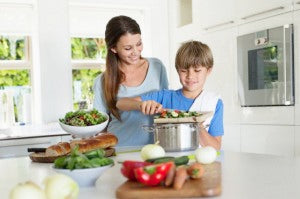 Mother and son (6-7) preparing food in kitchen