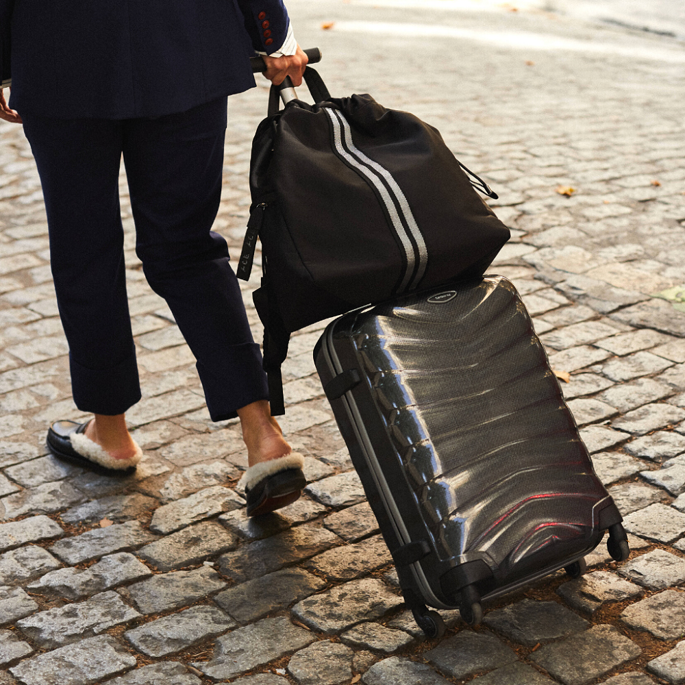Woman traveling with a ACE Bagpack color Black made with ECONYLu00ae regenerated nylon
