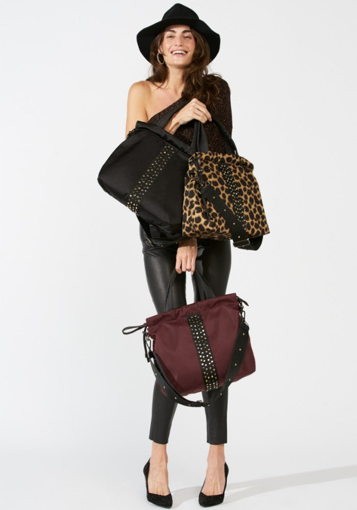 Woman carrying a ACE Urban Tote Bag color Black Leopard Burgundy made with ECONYLu00ae regenerated nylon