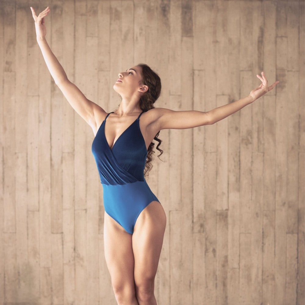 Dancer wearing the Coppelia leotard in blue Aisy Dance made with ECONYLu00ae regenerated nylon