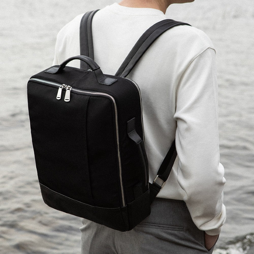 Man carrying The Gallery Backpack aoifeu00ae color Black made with ECONYLu00ae regenerated nylon