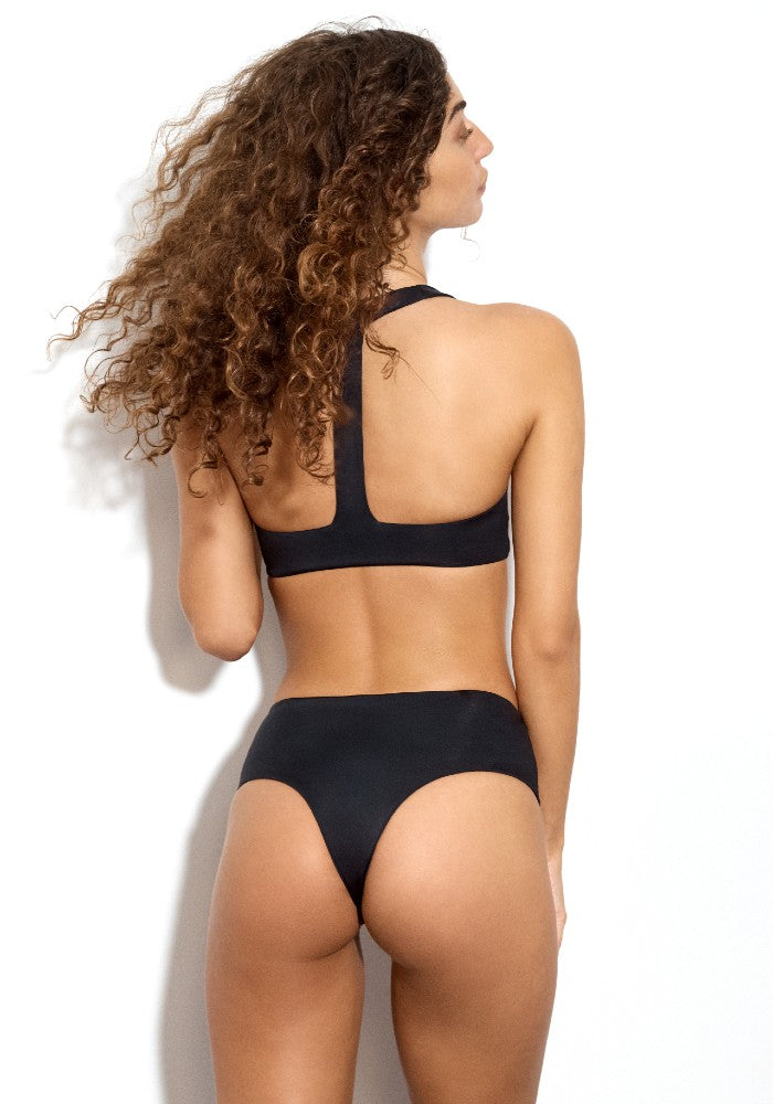 Back view of the Lola Square: The Modern Square Cheeky Bikini Bottom by Dos Gardenias color Black made with ECONYLu00ae regenerated nylon