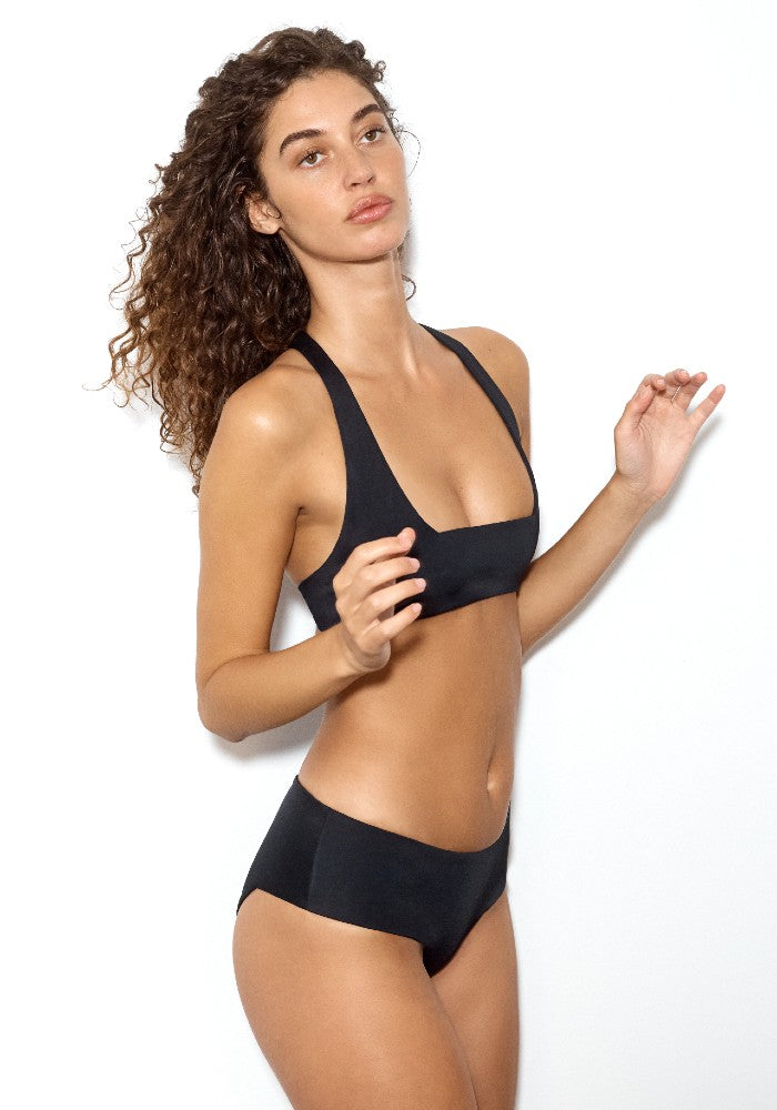 Side view of the Lola Square: The Modern Square Cheeky Bikini Bottom by Dos Gardenias color Black made with ECONYLu00ae regenerated nylon