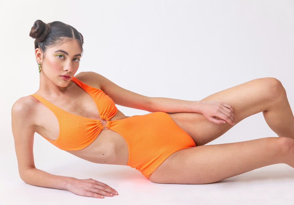 Woman wearing the Hawaii (Rainbow Collection) Swimsuit Mermazing color Orange made with ECONYLu00ae regenerated nylon