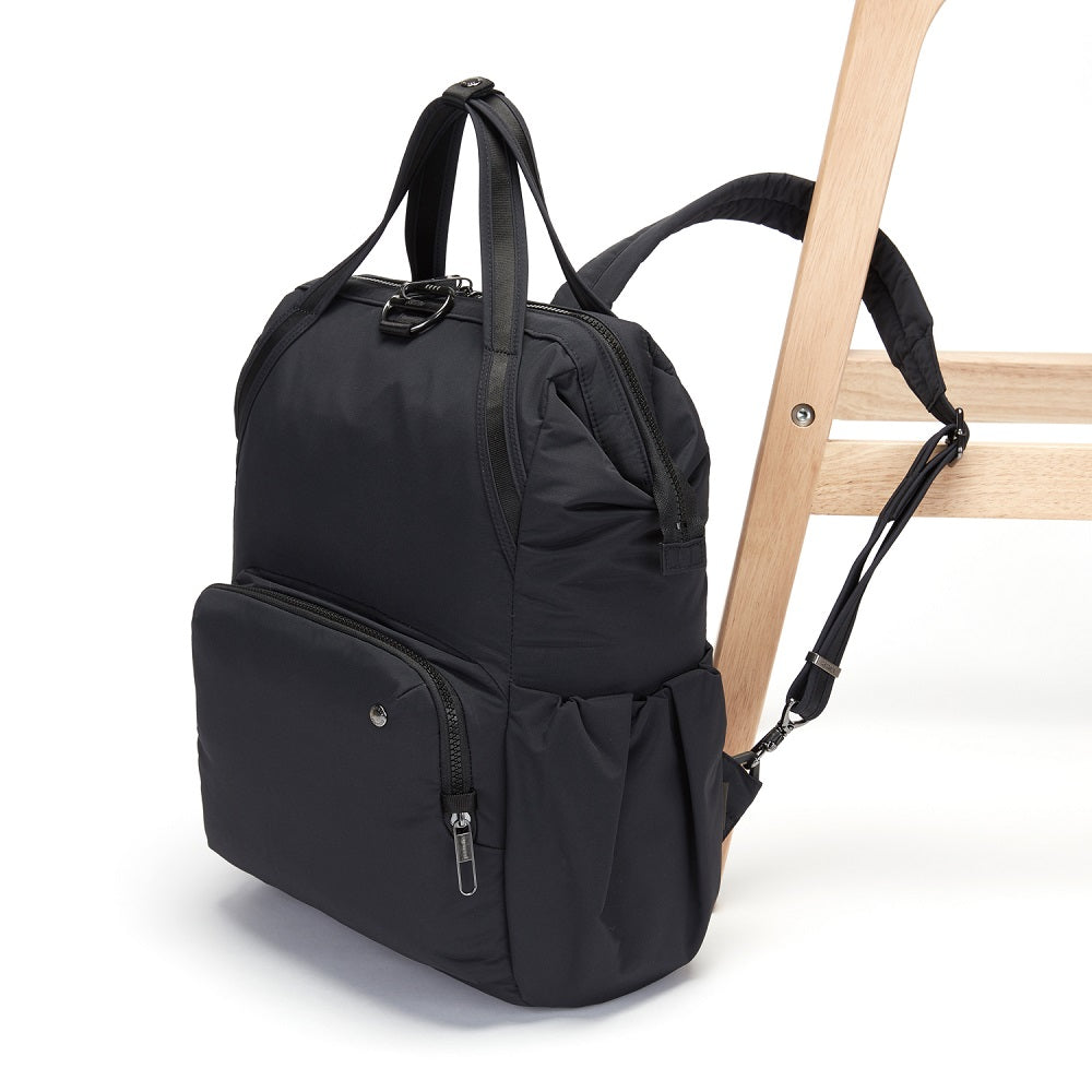 Side view of the Pacsafe Citysafe CX Anti-Theft Backpack color Black made with ECONYLu00ae regenerated nylon locked to a chair