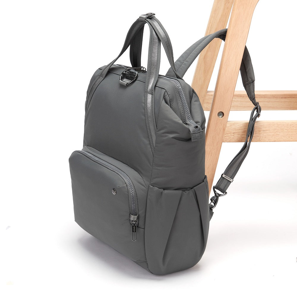 Side view of the Pacsafe Citysafe CX Anti-Theft Backpack color Storm made with ECONYLu00ae regenerated nylon locked to a chair